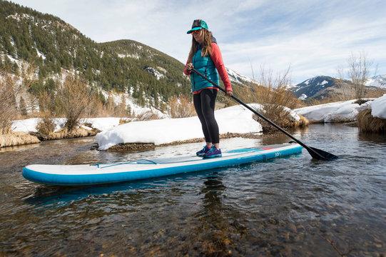 Woman paddle boarding in river in winter, Aspen, Colorado, USA