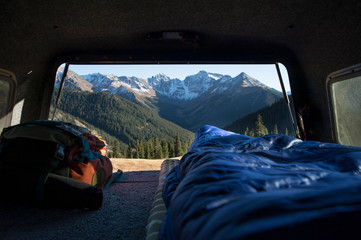 Mountain views from sleeping bag in the back of a truck