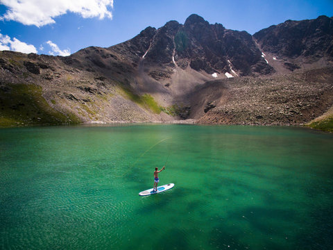 Young man fishing from paddle board on lake in Colorado, USA