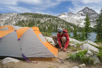 Man setting up tent by Toxoway Lake