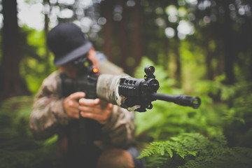 A soldier takes aim with his automatic weapon.