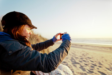 A woman takes a picture of the sunset with her smartphone while at the beach.