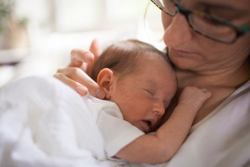 Close-up of newborn baby girl sleeping in her mothers arm