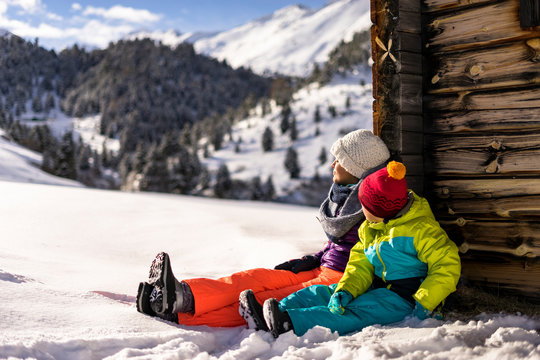 Mother and son sitting outside log cabin in winter in Austrian Alps, Obergurgl, Tyrol, Austria