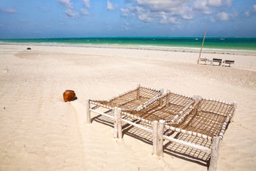 Wall Mural - White  sand beach with wooden deck chairs in Zanzibar, Tanzania