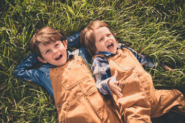 Two brothers lying on meadow