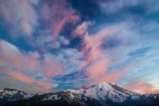 Alpenglow illuminates the clouds above Mount Ranier in Mount Ranier National Park.
