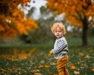 Portrait of toddler boy standing in park in autumn