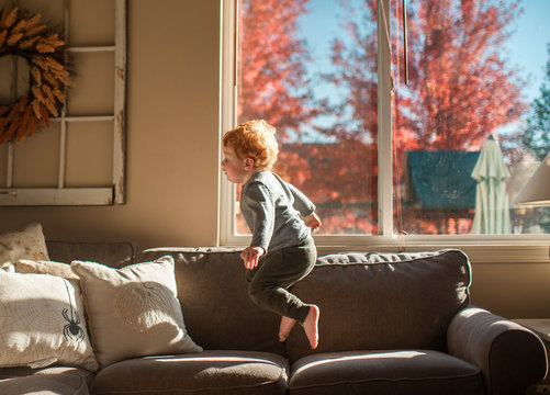 Toddler boy jumping on couch in living room