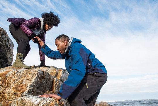 Woman helping man up rock outcrop
