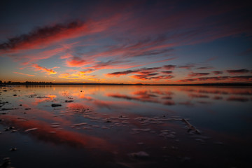 Colorful sunrise and clouds reflection over lake