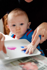Mother helping baby paint on paper