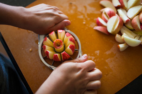 Person slicing apple with apple slicer