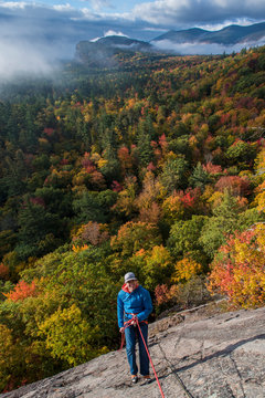 Front view of climber standing on front of colorful forest, North Conway, New Hampshire, USA