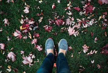 View of woman's feet standing in grass with fallen autumn leaves