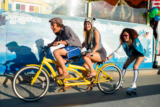 Young man pedals tandem with girl on back seat and another girl hanging on riding roller skates.