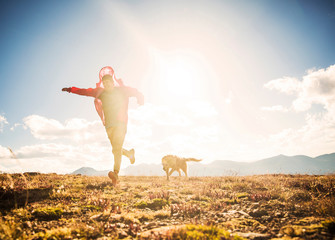 A smiling man runs with dog during sunset in front of a large mountain range