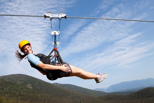 A woman smiles while riding on the longest zip line in Montana at 1,800 foot long and 300 feet off the ground at Whitefish Mountain Resort in Whitefish, Montana.