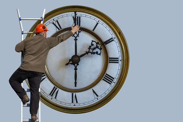 Man is standing on a ladder and adjusting the clock