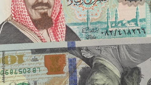 Saudi Arabia riyal against US dollar bill rotating  Saudi