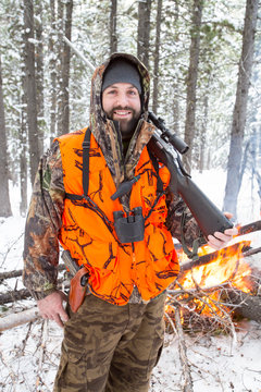 A male hunter in camouflage with a blaze orange vest on holds his rifle next to a fire he started when the weather turned colder during an elk and deer hunting trip in Northwest Montana.
