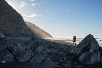 Female backpacker hiking along coastal cliffs