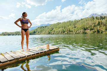 A Woman Is Standing On A Jetty After A Swim In Long Lake Along The Mccarthy Road, Alaska, Usa