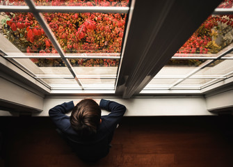 Young boy sitting on floor looking out window from high angle
