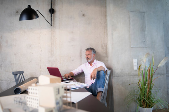 Businessman in a loft using laptop with documents and architectural model on table