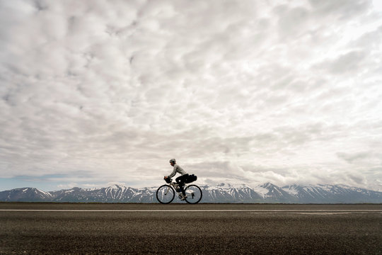 A cyclist riding along a road against snowcapped mountains