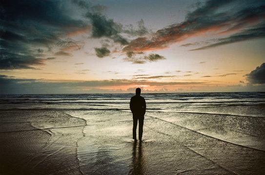 Silhouette of man on beach at sunset, Oregon, USA
