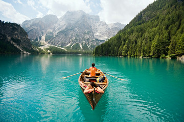 Couple in row boat on azure Lago di Braies, Italy