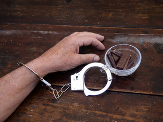 A man handcuffed to a cup with chocolate. Food or chocolate addiction concept