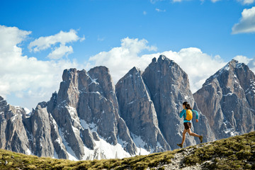 Woman running on trail in Dolomites mountains
