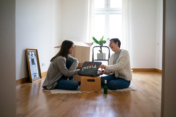 Young women sitting on floor of their new home, eating pizza
