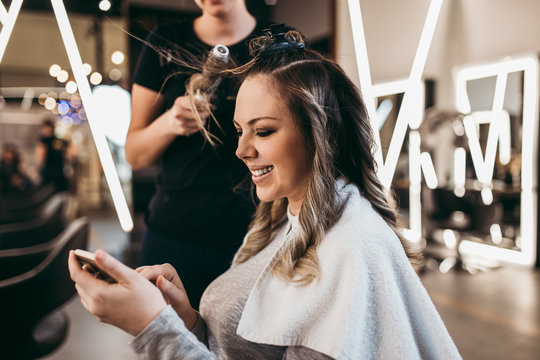 Beautiful woman with long hair at the beauty salon using smart phone and choosing hairstyle while getting a hair blowing. Hair salon styling concept.