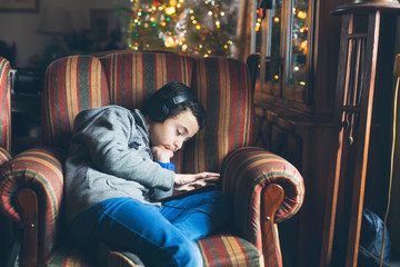 Boy in headphones using tablet in armchair at home