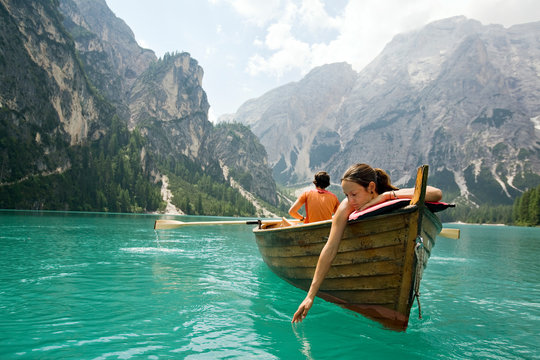 Couple in a row boat on azure Lago di Braies, Italy