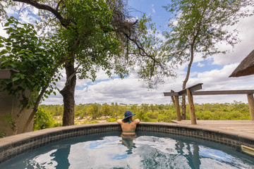 Woman relaxing in swimming pool at Londozi Safari Lodge, Sabi Sands Game Reserve, Mpumalanga, South Africa