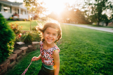 Little girl playing bubbles in yard during sunset