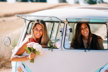 Two lesbian women have fun in a vintage classic van.
