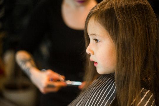 a little girl sits in a salon chair getting a haircut