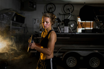Woman lifting weights in garage