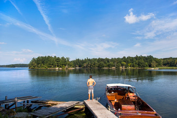 A young man stands on the edge of a dock next to a wooden boat on a clear day in the 1000 islands area of upstate New York.
