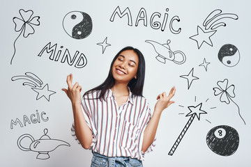 I am making my dreams true. Smiling young asian women in striped shirt holding fingers crossed while standing against grey background with hand drawn magic tools on it