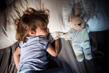 Young girl sleeping with teddy bear in bed