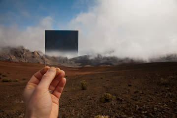 A man holds up a photographic graduated neutral density filter while standing in a volcanic cones within the Haleakala crater.