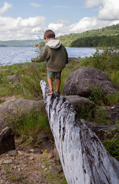 A four-year-old boy plays by Black Bear Cove on Aziscohos Lake in Lincoln Plantation, Maine