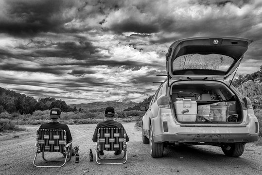 Rear view of two men sitting next to a Subaru outback car