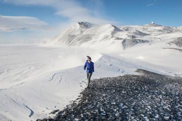 Woman trail running on Hut Point Peninsula on Ross Island, Antarctica